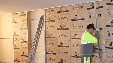 un expert pose de l'isolation sur les murs lors d'un chantier